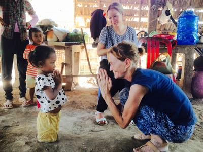 A volunteer greeting a young girl in Cambodia