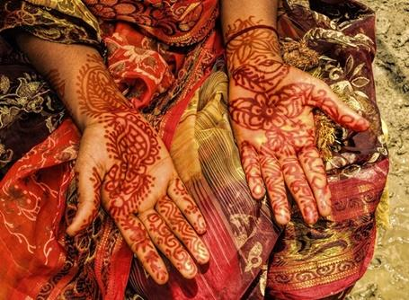 A local Bangladeshi woman displays her hands, which have been decorated with traditional henna patterns
