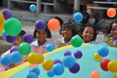 Children with colourful balls playing at care project in Thailand