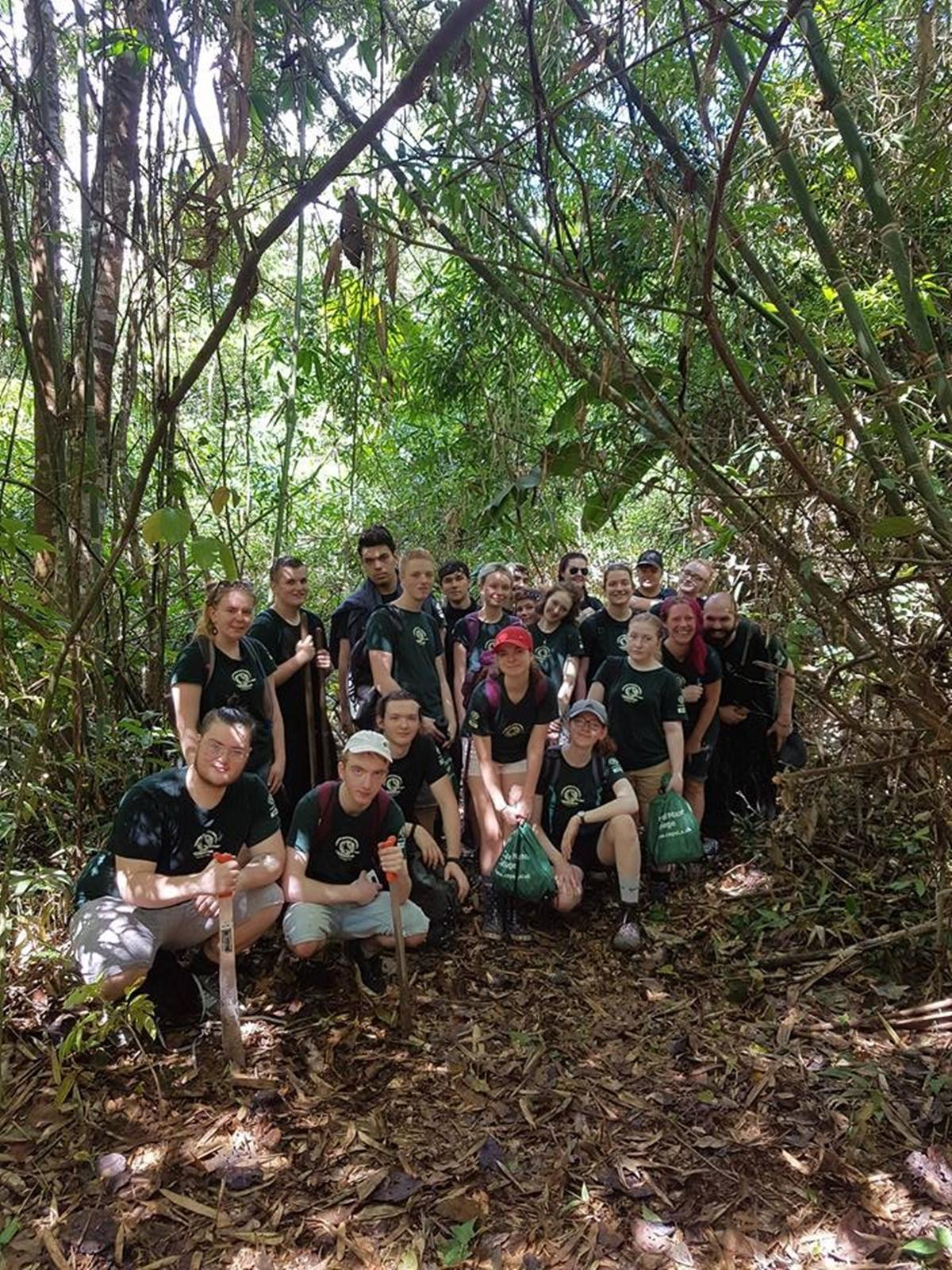 Cutting their way through thick vegetation, one of the groups pause for a photo