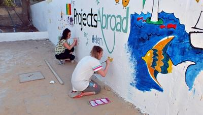 Female volunteers using their artistic skills to beautify a wall