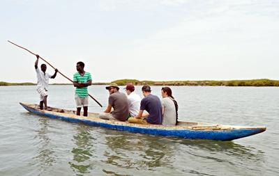 Projects Abroad volunteers from Italy, the USA, Canada and Belgium on a Pirogue boat at Joal-Fadiouth island in Senegal
