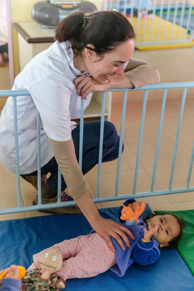 A young child at a nutrition centre being cared for by a Care volunteer in Bolivia