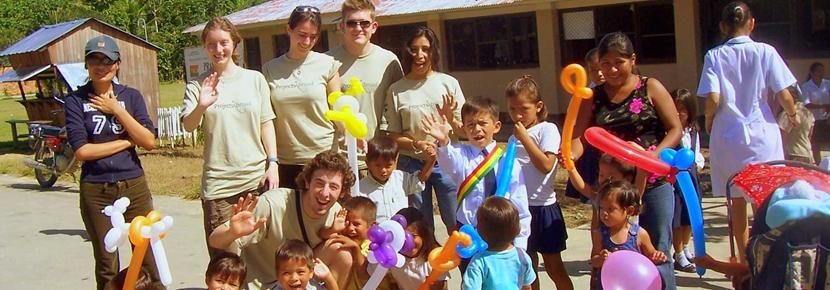 A group of volunteers helps the Bolivian children with a fun balloon activity