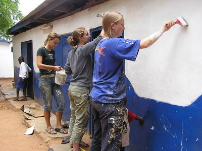 Young female volunteers painting a house in Ghana, housing project