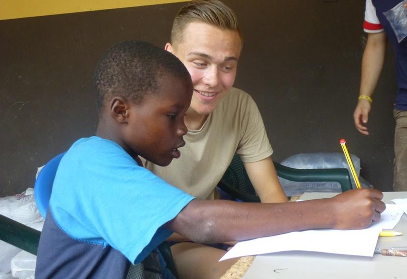 A student in Ghana is assisted by a Teaching volunteer