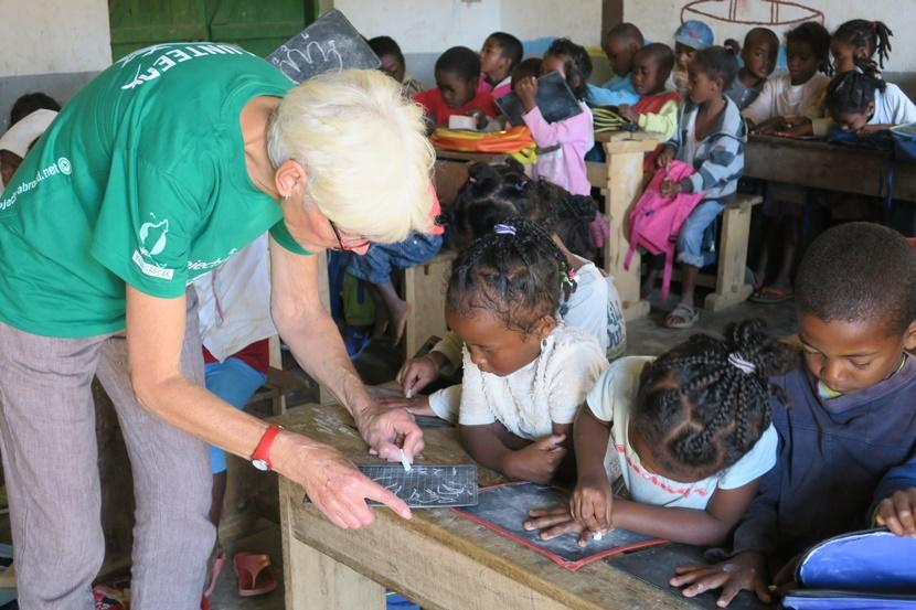 A volunteer helps a child trace her hand on a chalkboard