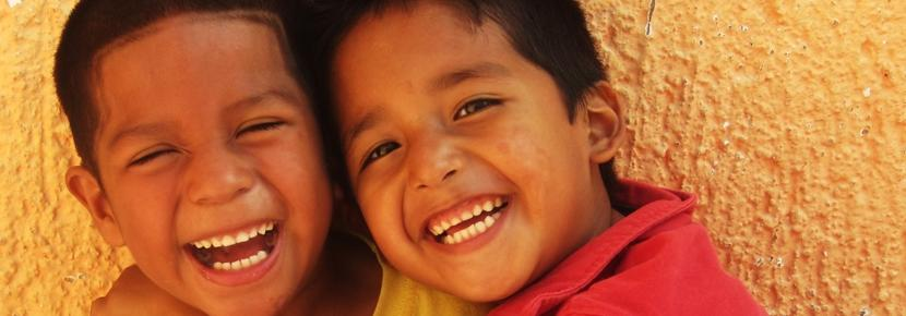 Two Mexican children laughing at having their photo taken