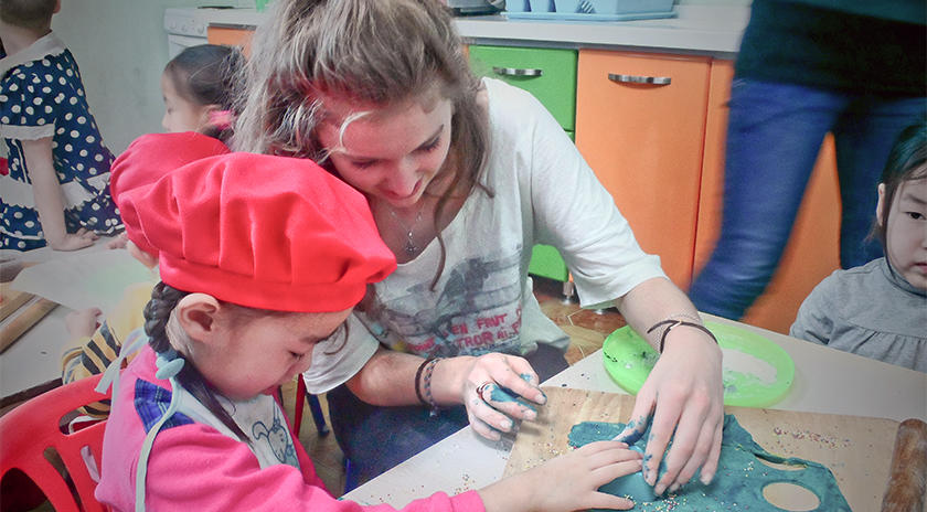 A care volunteer showing a child how to make cookies