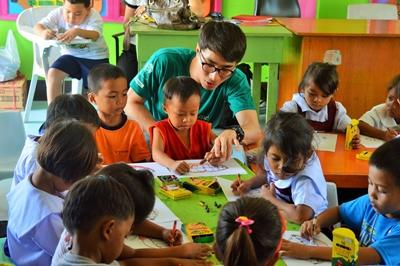 A volunteer busy teaching children in a care project in Philippines
