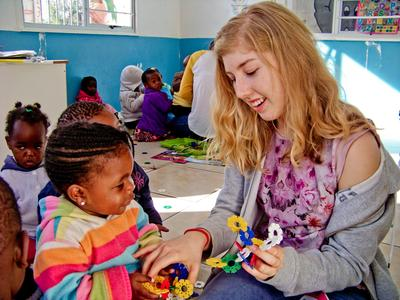 A child plays with a female volunteer in a care project in South Africa