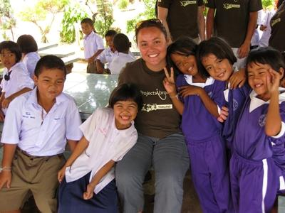A volunteer helps children at a local school in Thailand