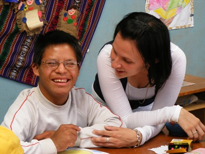 A volunteer helping to teach students at a special needs centre in Peru