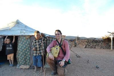 A volunteer kneels next to his host family during his nomadic placement.