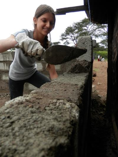 Volunteer plastering at building project in Tanzania, Africa