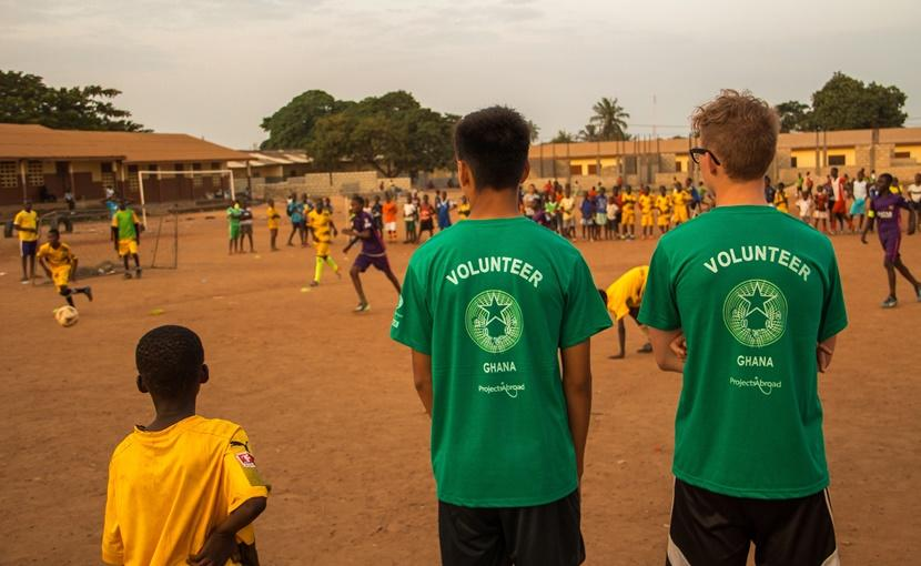Volunteers watch their students play a soccer match in Ghana