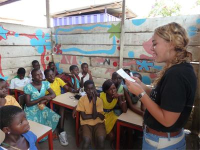 A female volunteer teaches her class while on a group trip abroad.