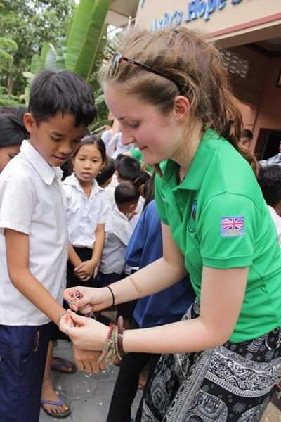Girl guide volunteer playing with child in Cambodia