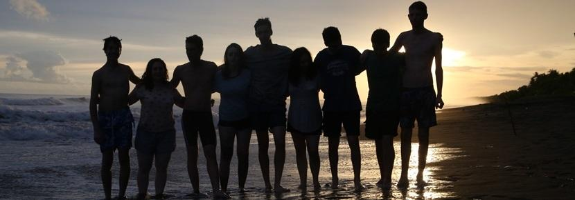 A group of students from London's JFS School pose for a photo at sunset on Matapalo Beach during a weekend excursion to Costa Rica's Central Pacific Zone