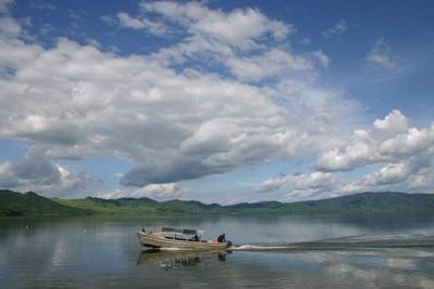 A boat crossing a picturesque lake in Ghana