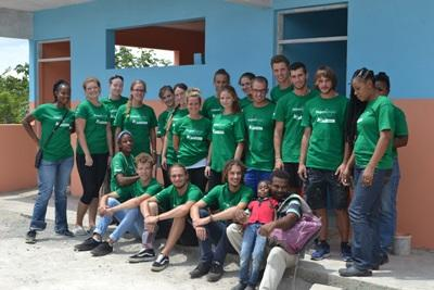 Projects Abroad volunteers paint a bathroom at the Old England Primary School during a community day activity in Jamaica.