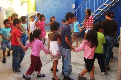 A group of children at a care centre enjoying some fun games with the volunteers