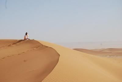 A volunteer relaxes on top of a sand dune in the desert during their free time