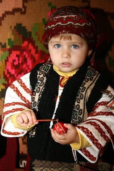 A child plays with her toy against a rose tapestry in Romania