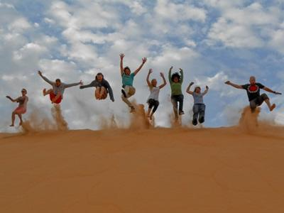 Group of volunteers having fun on sand dunes in Senegal, Africa