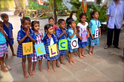 A group of children from a preschool welcome the volunteers with a sign
