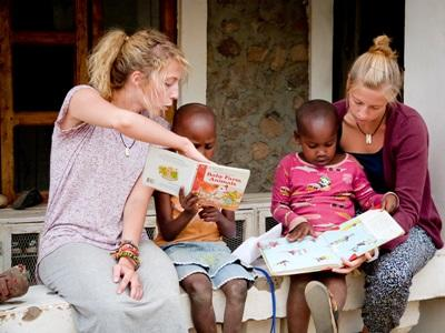 Two volunteers helping to teach Tanzanian children to read