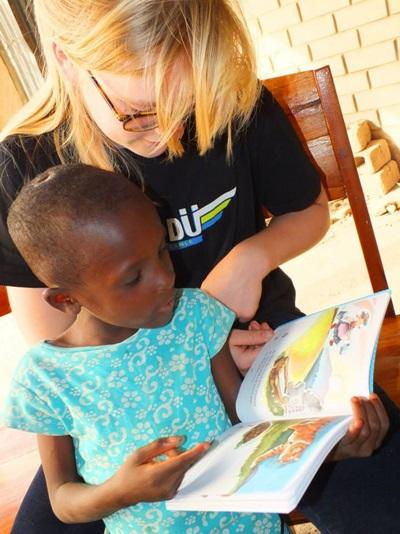 A volunteer teaching a child in Togo to read